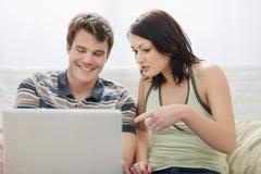 Girl showing to boyfriend something in laptop Stock Image