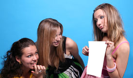 A girl showing to her friends a list of paper Stock Photos