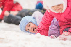 Girl showing tongue rolled down a hill and fell into the snow. Two girls in the winter ride on a snowy hill surrounded by other children Stock Photo