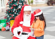 Girl Showing Wish List To Santa Claus Royalty Free Stock Photos