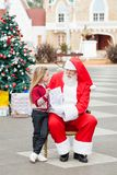Girl Showing Wish List To Santa Claus Royalty Free Stock Photography