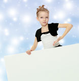 The girl shows an advertisement banner with a finger. Stock Photo