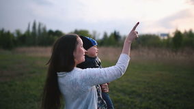 Girl shows baby something in the sky stock footage