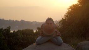 Girl shows baddha padmasana with forward bending slow motion. Yoga teacher shows baddha padmasana with forward bending on huge rock against tropical trees low stock video footage