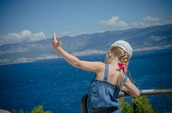 Girl shows a bird with a sea view Royalty Free Stock Image