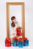 Girl shows box with gift and looks out from frame. Girl shows box with gift and looks out from gilt frame standing among red and blue gift boxes stock photos