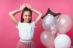 Girl shows Bunny ears, birthday party on pink background, with balloons stock photo