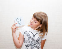 Girl shows card with  sign. Little girl show in right hand card with idea sign Stock Images
