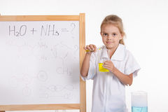 Girl shows chemical experience standing at the blackboard Stock Images