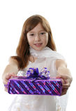 The girl shows the christmas gift. The girl in a white dress shows the christmas gift Royalty Free Stock Photos