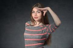 Girl shows curiosity against a dark background Stock Photo