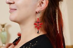 The girl shows ornaments from macrame. The girl shows the decorations from the macrame earrings Royalty Free Stock Photo