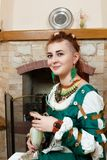 The girl shows ornaments from macrame. The girl shows the decorations from the macrame necklace, bracelet and earrings on the background of the fireplace Stock Photos