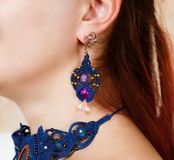 The girl shows ornaments from macrame. The girl shows the decorations from the macrame necklace and earrings Royalty Free Stock Photos