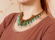 The girl shows ornaments from macrame. The girl shows the decorations from the macrame necklace Stock Image