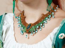 The girl shows ornaments from macrame. The girl shows the decorations from the macrame necklace Stock Photo
