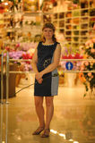 Girl shows emotions. Girl standing at the entrance to the store and holding a rose Stock Image