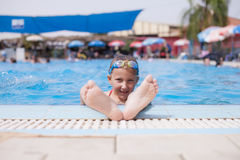Girl shows feet from the pool Royalty Free Stock Photography