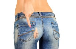 The girl shows a finger hole on the pope in old torn jeans. isolated.  Royalty Free Stock Photo