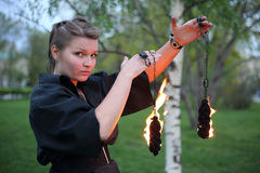 A girl shows a fire show with chain. A girl in a black dress shows a fire show with chain Royalty Free Stock Photography