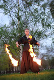 A girl shows a fire show on nature stock photography