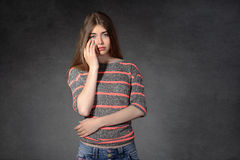 Girl shows a grudge against a dark background Royalty Free Stock Photos