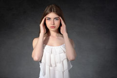 Girl shows that she had a headache against a dark background Royalty Free Stock Photo