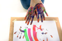 Girl shows hands in the paint Stock Images