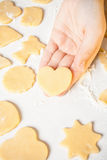 Girl shows heart shape out of dough Stock Image