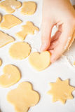 Girl shows heart shape out of dough Royalty Free Stock Image