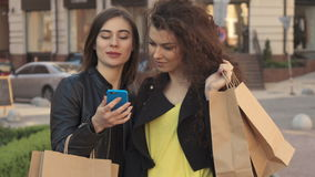 Girl shows her friend something on her smartphone on the street of the city stock video footage