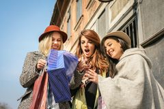 Girl shows her friends new clothes. Tree best friend enjoying in Stock Image