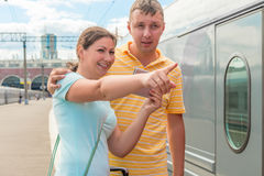 Girl shows her husband the direction of the train Stock Photo