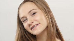 Girl shows her smile braces. White. Slow motion