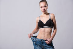 Girl shows her weight loss by wearing an old jeans Royalty Free Stock Images