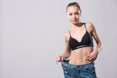 Girl shows her weight loss by wearing an old jeans Stock Photos
