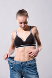 Girl shows her weight loss by wearing an old jeans Stock Photography
