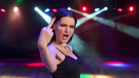 Girl shows middle finger in anger at the party. Girl in evening dress showing middle finger in anger at the party in the dark with flood lights stock video footage
