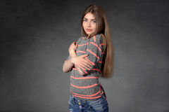Girl shows modesty or shyness against a dark background Stock Photography