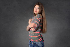 Girl shows modesty or timidity against a dark background Stock Photography