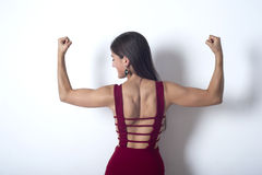 Girl shows the muscles in her arms. Girl in a red dress shows the muscles in her arms Royalty Free Stock Photography