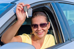 Girl shows off the key to the new car Stock Photography
