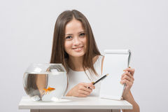 Girl shows a pen entry pad, standing next to an aquarium with goldfish Royalty Free Stock Photography
