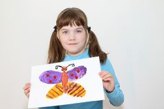 Girl shows picture with butterfly royalty free stock image