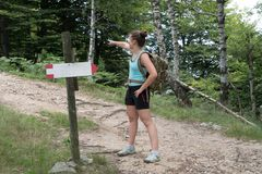 Girl shows the right direction during a mountain hike royalty free stock images