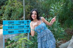 The girl shows on the road sign, indicates the direction of the path.  royalty free stock photo