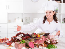 Girl shows sausages and smoked products Royalty Free Stock Photography