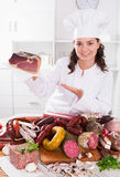 Girl shows sausages and smoked products Royalty Free Stock Images