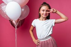 Girl shows shows two fingers, portrait of teen girl on pink background, with balloons stock images