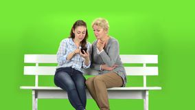 Girl shows something in the phone to her mother. Green screen stock footage